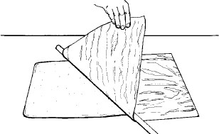 Figure 13-35 A second method of removing the baking paper; holding a dowel against the baking paper and sponge to prevent the sponge from pulling up with the baking paper and tearing as the paper is pulled away with the other hand