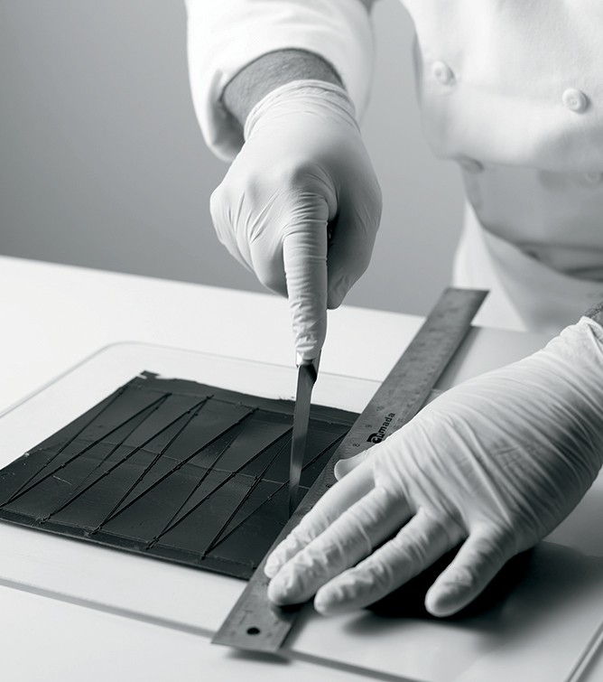When the chocolate is halfway crystallized, cut the chocolate using a shaped cutter or the back of a paring knife and a ruler if necessary.
